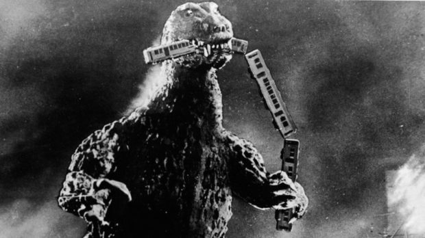 Radioactive monster Godzilla stomps through a city and eats a commuter train in a scene from Godzilla, King of the Monsters!, directed by Ishiro Honda and Terry O. Morse. The 1956 film was a re-edited version of the 1954 Japanese film Gojira, directed by Honda.